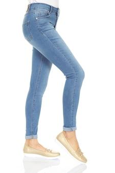 Jambes de femme avec un denim bleu sur fond blanc