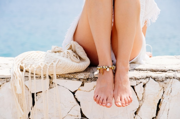 Jambes de femme gros plan avec bracelet au bord de la mer