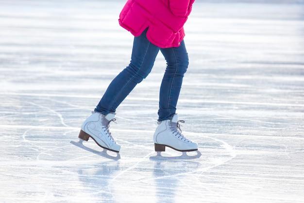 Jambes d'une femme en jean bleu et patins blancs sur une patinoire. passe-temps et loisirs. sports d'hiver