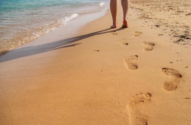 Jambes de femme marchant sur la plage laissant des empreintes de pas en gros plan