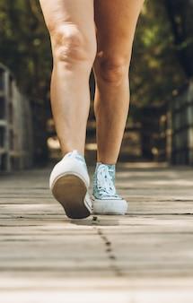 Jambes d'une femme marchant sur un pont en bois