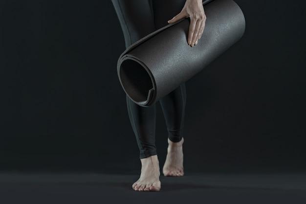 Jambes de femme marche pratiquant le yoga sur tapis de yoga