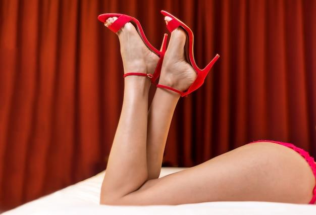 Jambes de femme parfaites minces en sandales à talons hauts rouge, allongé sur le lit.