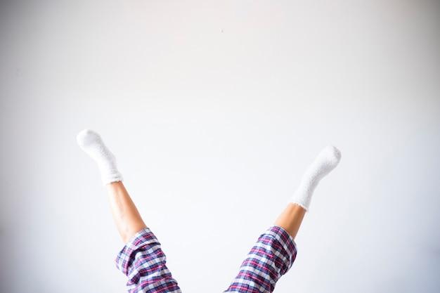 Jambes de femme en position inversée avec fond de mur de salle blanche - concept d'exercices de remise en forme à la maison et personnes saines et drôles de style de vie - copyspace et votre texte ici