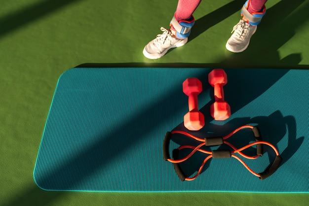 Jambes de femme près de tapis avec extenseur et haltères