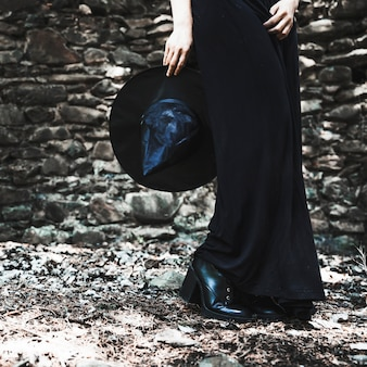 Jambes de femme en robe noire tenant un chapeau