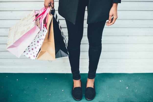 Jambes de femme avec des sacs colorés