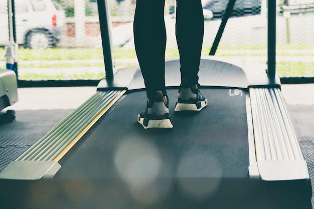 Jambes de femme sur tapis roulant ou machine de suivi dans un centre de fitness