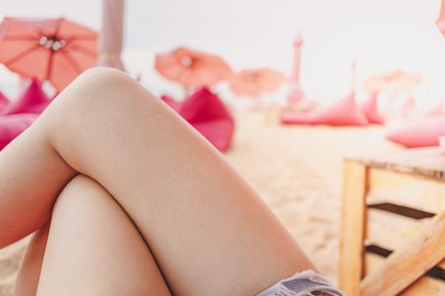 Jambes de femme avec vue sur le concept de café de plage de détente sur la plage d'été