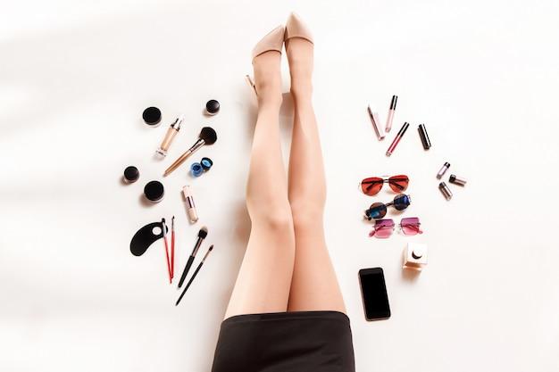 Jambes de femmes et accessoires élégants de mode d'été vue de dessus