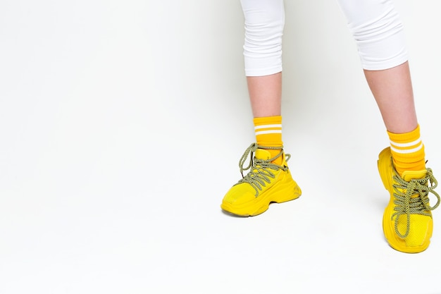 Jambes de femmes adolescentes en baskets jaunes sur fond blanc. photo horizontale
