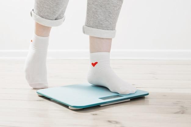 Jambes de femmes sur des balances électroniques sur un plancher en bois