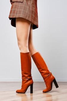 Jambes de femmes en bottes marron et collants blancs avec motif à pois