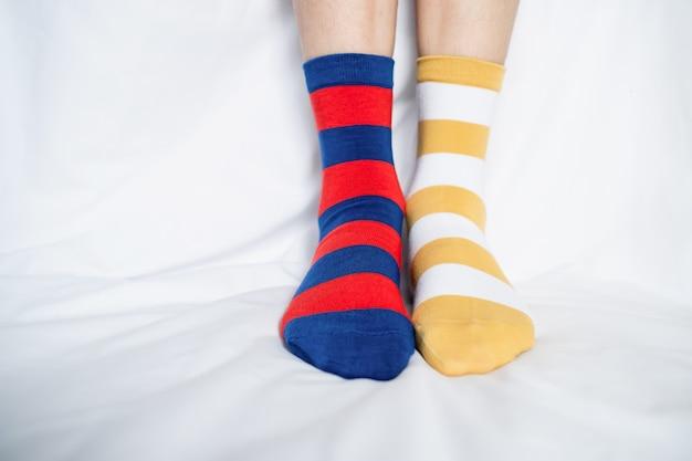 Jambes de femmes en chaussettes couleurs alternant, pied sur le sol en tissu blanc.