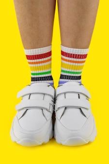 Jambes de femmes en chaussettes multicolores dans les baskets blanches sur fond coloré, gros plan, image verticale