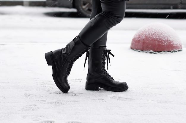 Jambes de femmes en chaussures d'hiver noires