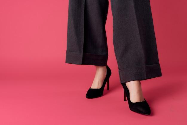 Jambes de femmes chaussures noires glamour luxe mur rose vue recadrée