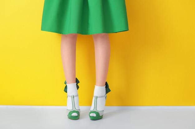 Jambes de femmes en chaussures à talons hauts verts et chaussettes sur la couleur