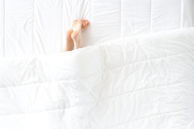 Les jambes des femmes dépassent des couvertures dans les problèmes de sommeil au lit et le concept d'insomnie