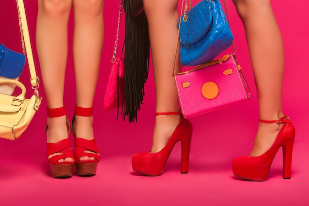 Jambes des femmes. femmes méconnaissables tenant des sacs et des sacs à main. mesdames portant des chaussures rouges sur le mur rose.