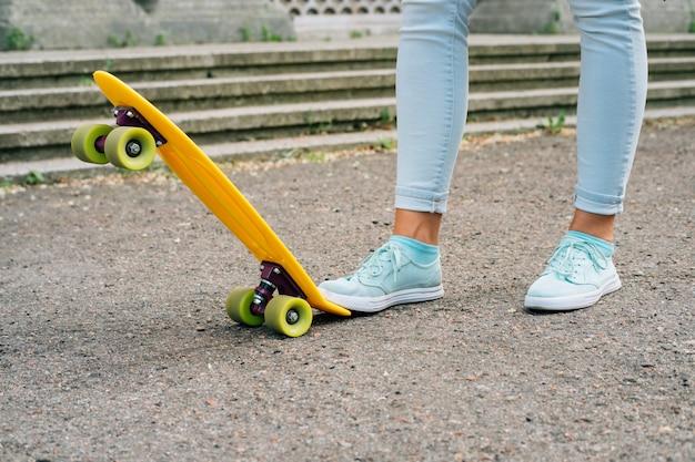 Jambes de femmes en jeans et baskets debout à côté de skate
