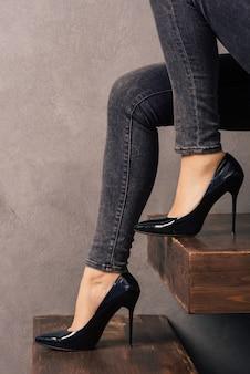 Jambes de femmes en jeans et chaussures en cuir verni à talons hauts sur une échelle en porte-à-faux en bois