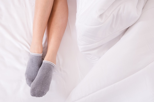 Jambes de femmes sur un lit blanc