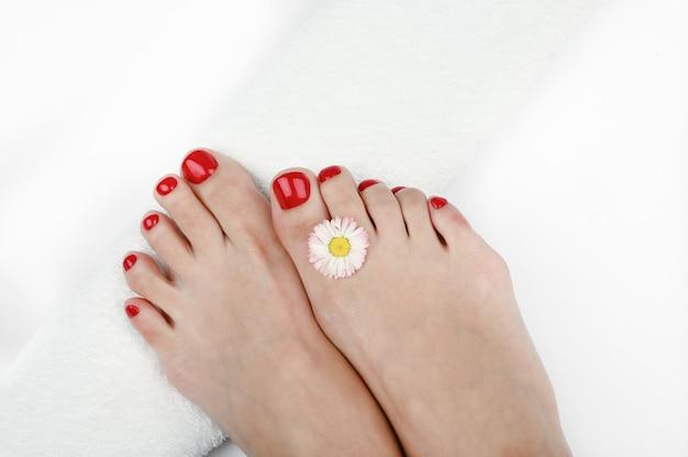 Jambes de femmes avec une serviette roulée blanche