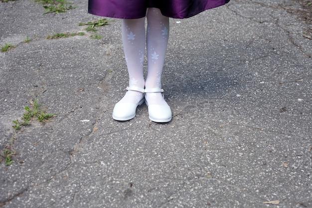 Les jambes de la fille en chaussures blanches et collants se tiennent sur la piste.