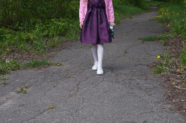 Les jambes de la fille en collants et chaussures fantaisie blancs. elle descend le chemin dans le parc.