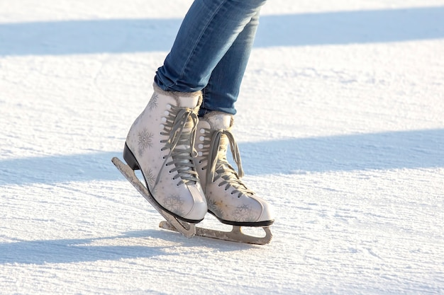 Jambes d'une fille en jean bleu et patins blancs sur une patinoire. passe-temps et loisirs. sports d'hiver