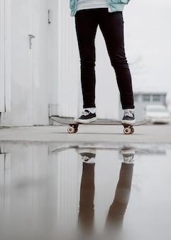 Jambes de fille patineuse debout sur sa planche à roulettes