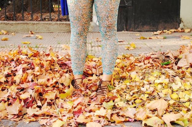Jambes d'une fille profitant des feuilles d'automne