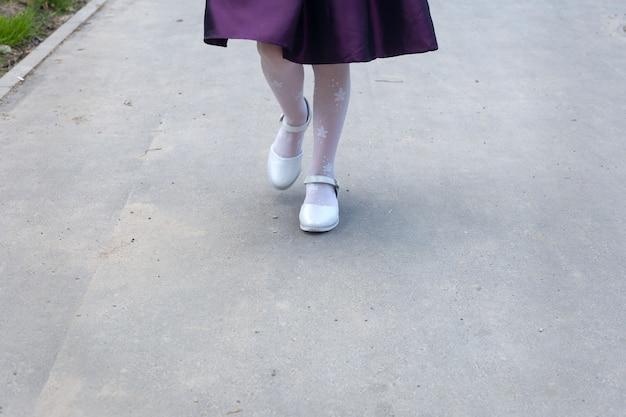 Les jambes d'une fille de six ans dans de beaux collants blancs et d'élégantes chaussures blanches