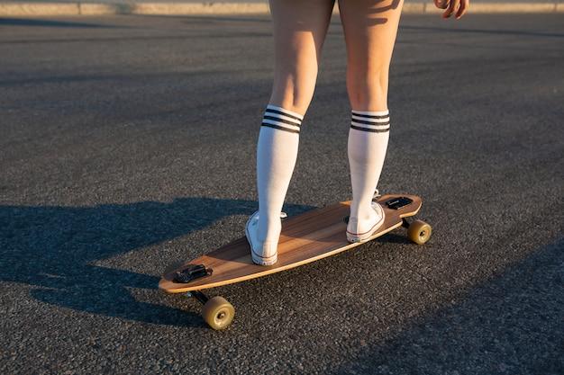 Les jambes de la fille sont sur le longboard, elle monte. marchez sur le journal le week-end. les pieds de la fille se tiennent sur le tableau. . fond