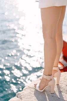 Jambes fines d'une femme en chaussures à talons sur le fond de la mer
