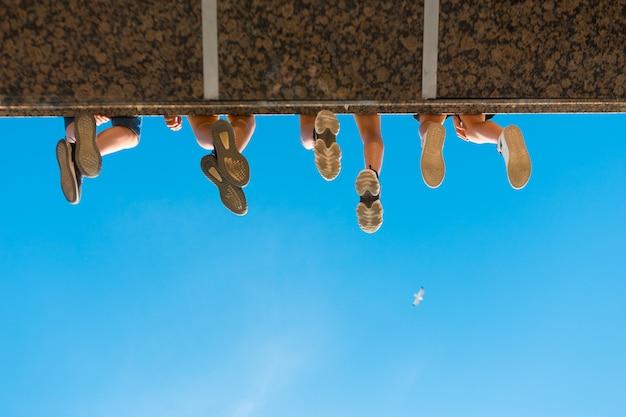 Jambes de garçons dans des chaussures suspendues au pont contre le ciel bleu