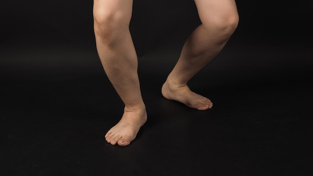 Les jambes de l'homme asiatique et les pieds nus raccourcissent est isolé sur fond noir