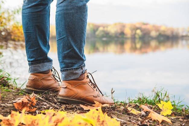 Les jambes de l'homme en bottes bouchent l'espace de copie de la saison d'automne