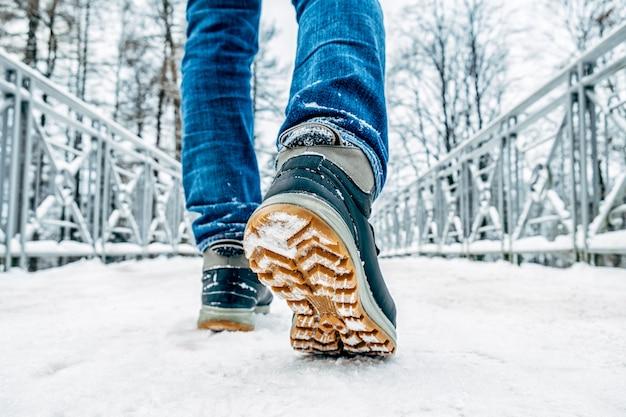 Les jambes de l'homme en bottes marchant dans la neige