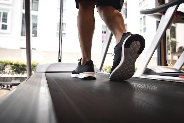 Jambes d'homme avec des chaussures de sport s'exécutant sur un tapis roulant dans une salle de fitness.