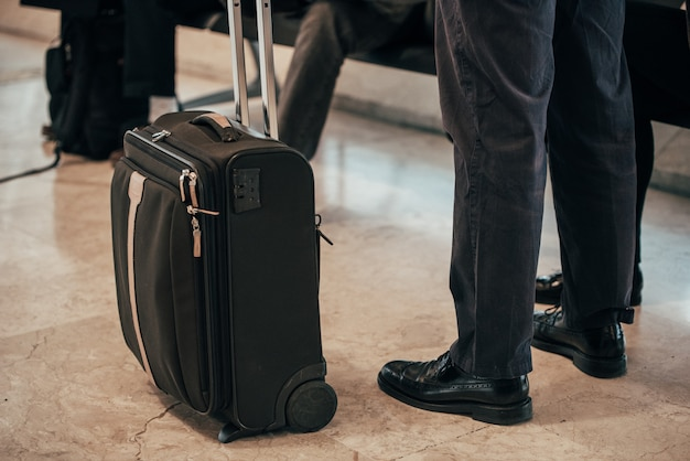Jambes d'homme debout bagages à l'aéroport