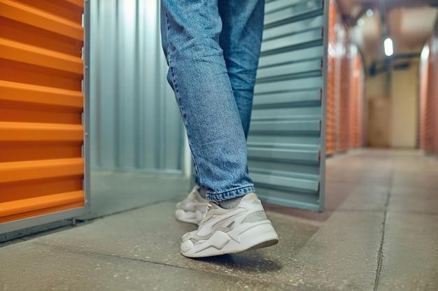 Jambes d'homme entrant dans la porte ouverte du conteneur