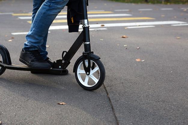 Les jambes d'un homme en jeans et baskets sur un scooter dans le parc en automne avec des feuilles jaunes sèches tombées sur l'asphalte. balades d'automne, mode de vie actif, transports écologiques, circulation
