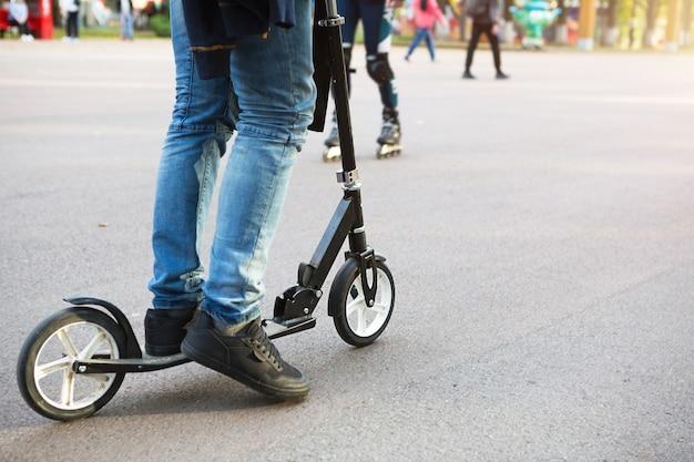 Les jambes d'un homme en jeans et baskets sur un scooter dans le parc sur une piste asphaltée. promenade sportive, mode de vie sain et actif, transports écologiques, circulation