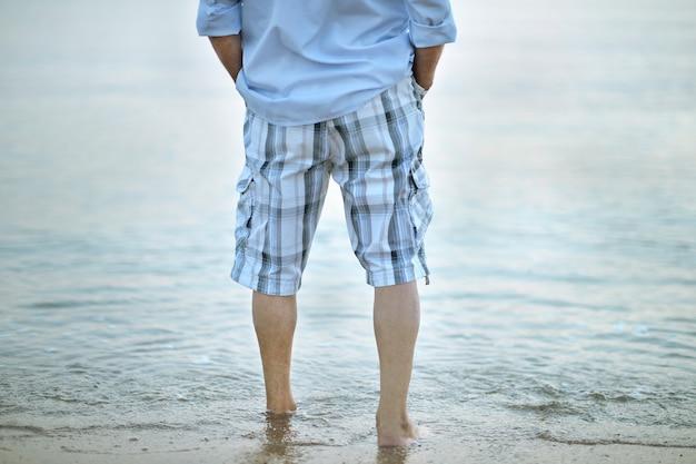 Jambes de l'homme marchant sur la plage libre
