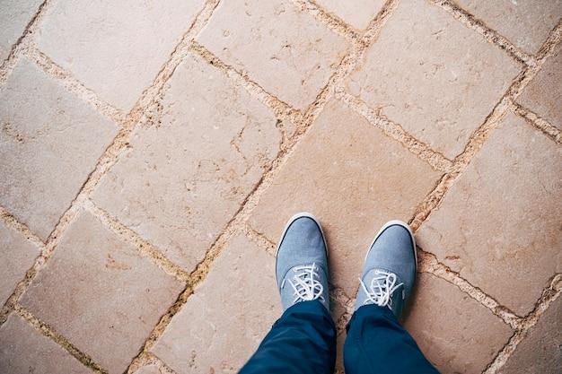 Jambes d'un homme en pantalon bleu et baskets bleues debout sur la route de pierre