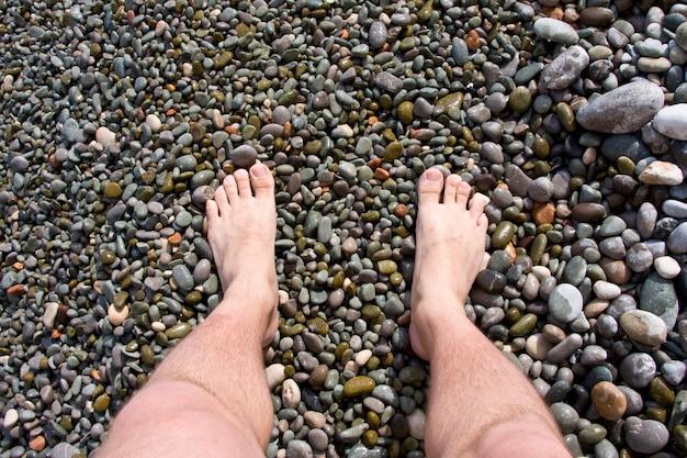 Les jambes de l'homme sur les pierres de la mer