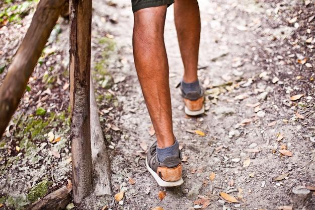 Jambes de l'homme sur le sentier du parc ou de la forêt avec closeup main courante