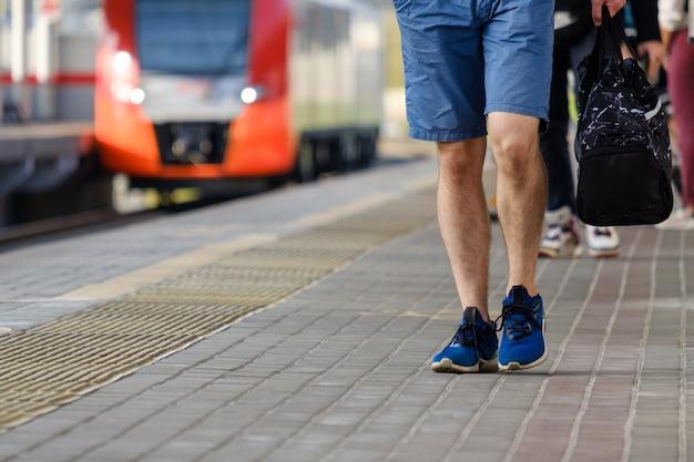Jambes d'un homme en short et baskets marchant le long de la plate-forme d'une gare un train arrivant sur une journée d'été ensoleillée